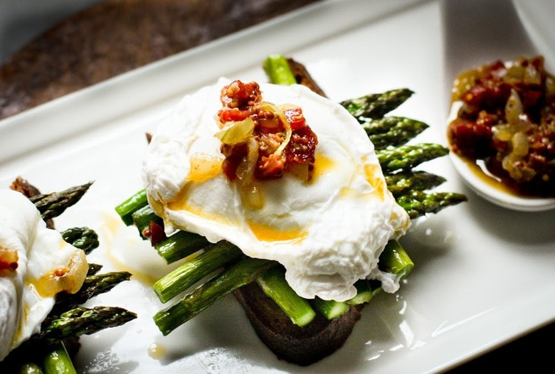A simple breakfast- Roasted asparagus on toast with poached eggs and a warm bacon vinaigrette. Or make this for dinner! | www.feastingathome.com
