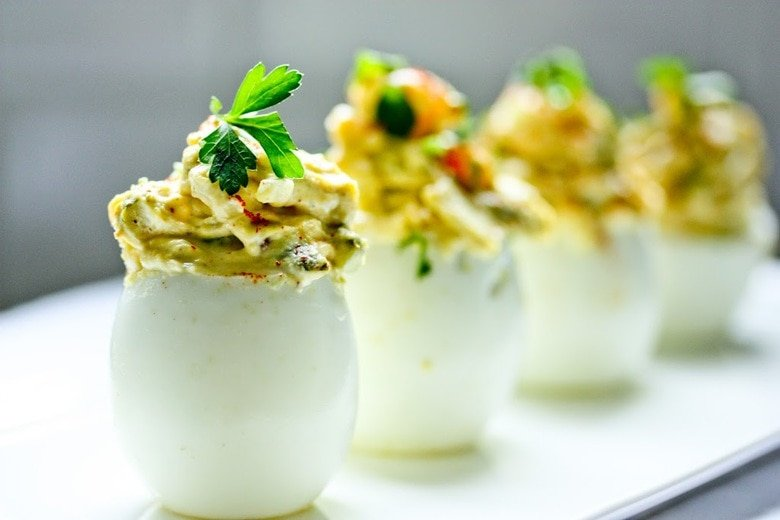 A simple delicious recipe for the Best EVER Deviled Eggs- Made with crumbled bacon, cheddar and onion. | www.feastingathome.com
