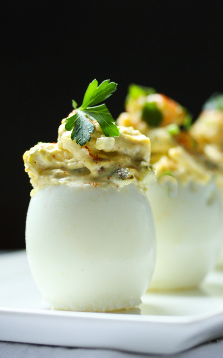 The Best EVER Deviled Eggs- Made with crumbled bacon ( or vegan bacon bits) cheddar and onion, simple and soooooo delicious! | #deviledeggs www.feastingathome.com #appetizer #partyappetizer