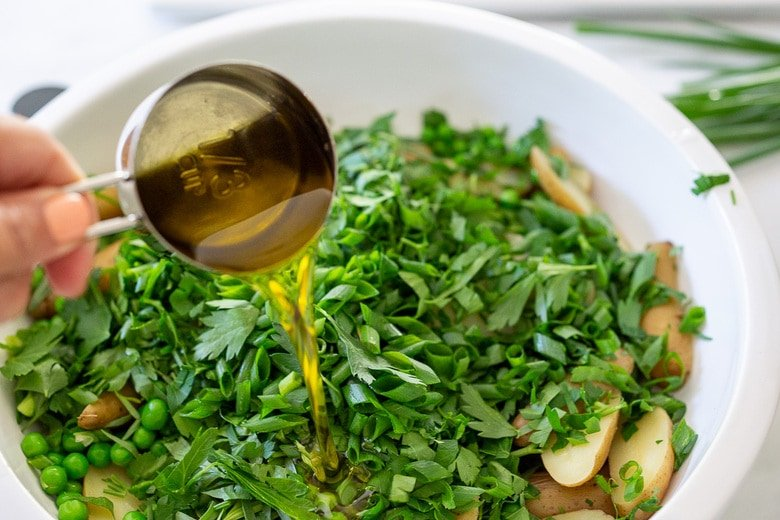 adding olive oil to the salad