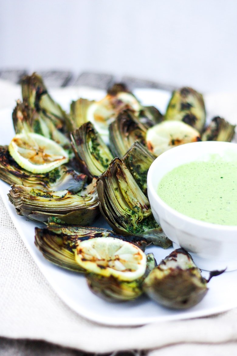 A recipe for Grilled Artichokes with EASY step-by-step instructions, served with Herbed Oil and optional Basil Aioli. Vegan adapatable!