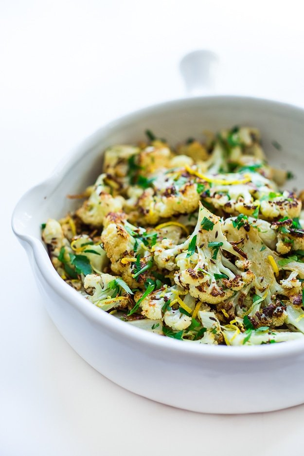 Roasted Cauliflower with garlic, lemon, parsley and coriander seeds - a simple vegan side dish that is full of flavor! Vegan and gluten free! |www.feastingathome.com #roastedcauliflower #cauliflower #vegansidedish