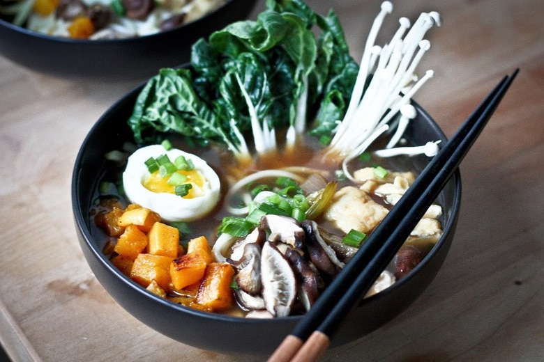 A warming bowl of Ramen with a flavorful VEGAN Shiitake Broth, smoked mushrooms ( optional) roasted veggies, wilted greens and tofu. | www.feastingathome.com