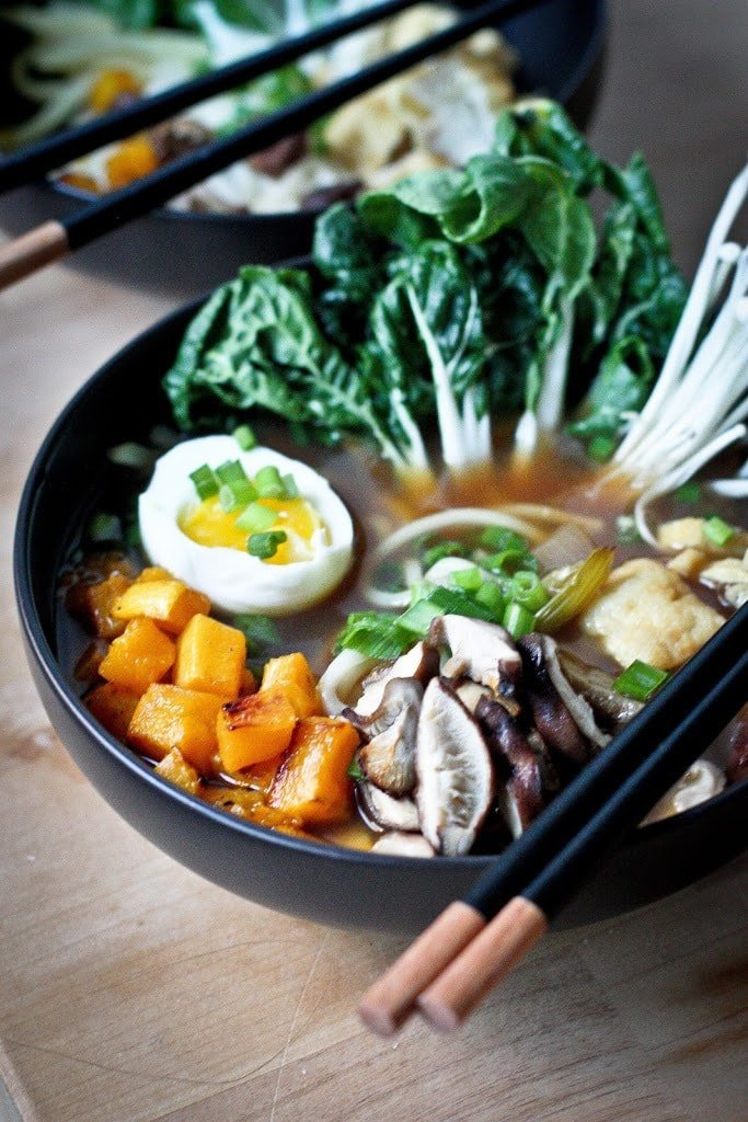 A warming bowl of  Ramen with a flavorful VEGAN Shiitake Broth, smoked mushrooms ( optional)  roasted veggies, wilted greens and tofu.   www.feastingathome.com