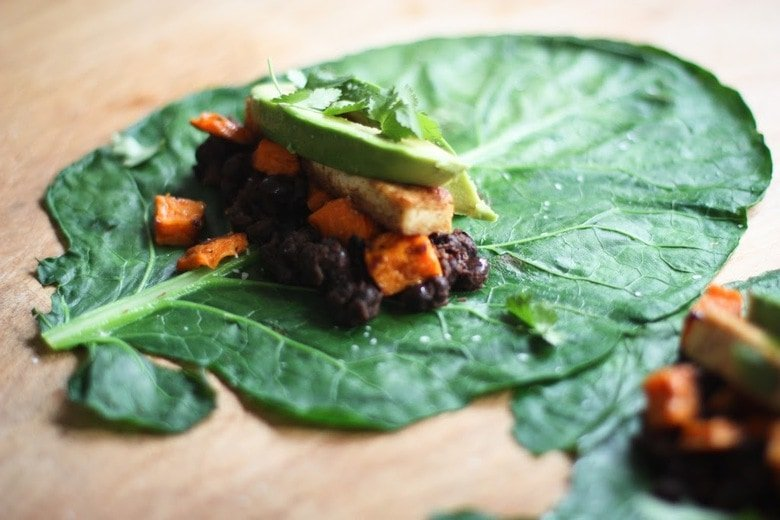 Healthy Vegan Collard Green Wraps - served up burrito-style with roasted sweet potatoes, tofu, chipotleblack beans, avocado and a delicious Chipotle Lime dressing. Vegan and Gluten free!#collardgreens #collardgreenwraps #collardgreenburritos #veganburrito #glutenfreeburrito