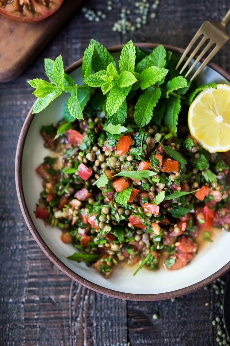 This Simple Lentil Tabouli Salad is full of Middle Eastern flavor! Filling lentils are paired with summer  tomatoes, lemon, mint and parsley and a unique combination of spices, and keeps for several days, perfect for midweek lunches or potlucks! Vegan and Gluten-Free #tabouli #lentil #lentils #lentilsalad #lentiltabouli #lentiltabbouleh #tabbouleh #vegan #salad #glutenfree