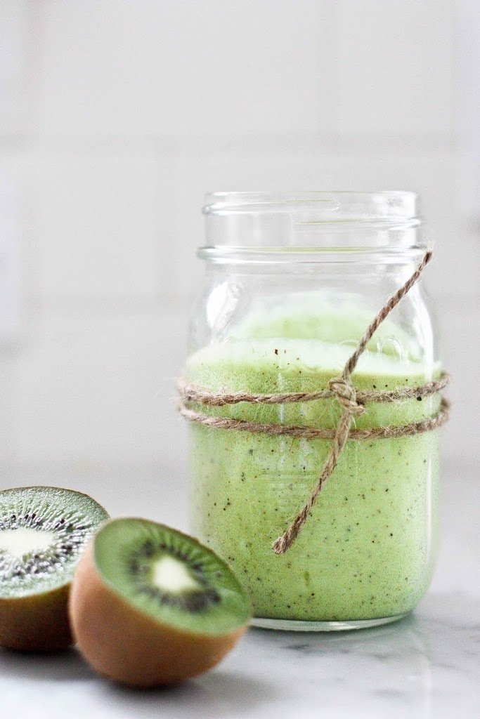 A simple tasty recipe for Avocado Smoothie with Kiwi and lime, sweetened with honey ( or maple). Deliciously addicting and easy to make!   www.feastingathome.com