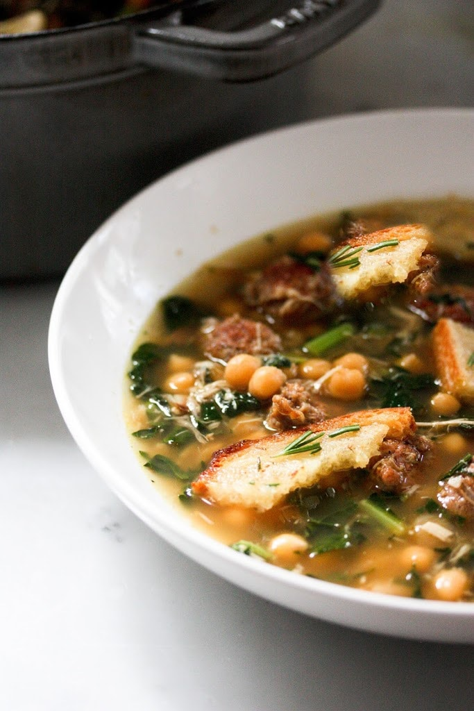 A brothy healing soup - Kale, chickpea and chicken soup with a toasty rosemary crouton. Simple and delicious.   www.feastingathome.com