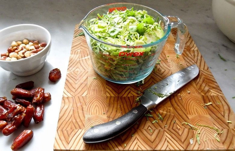Brussel Sprout Salad with Hazelnuts and Dates! This easy healthy vegan salad has a delicious combination of flavors and can be made ahead! | www.feastingathome.com #brusselsproutsalad #brusselsprouts #vegansalad #dates #brusselsproutslaw #shreddedbrusselsprouts