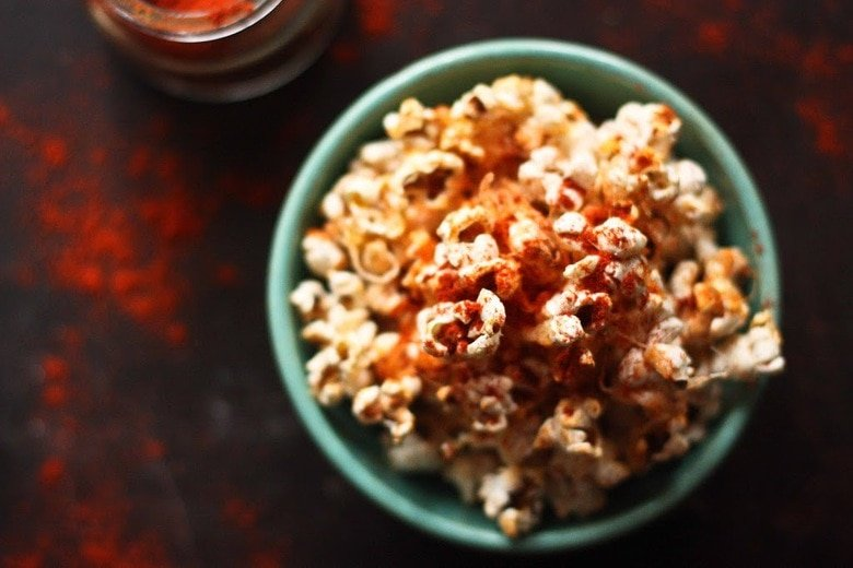 This stove-top recipe for Garlic Parmesan Popcorn is addicting! Sprinkled with smoked paprika, its the perfect snack for movie night. | www.feastingathome.com