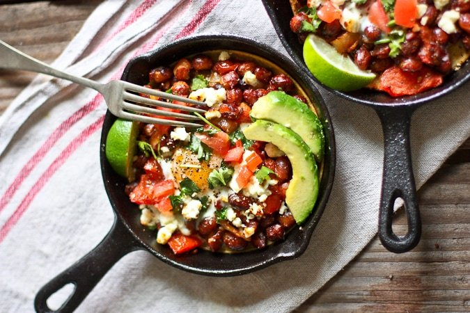 Skillet Huevos Rancheros- with hearty beans, crispy tortilla, avocado and fresh tomato and cilantro...so simple and tasty! | www.feastingathome.com
