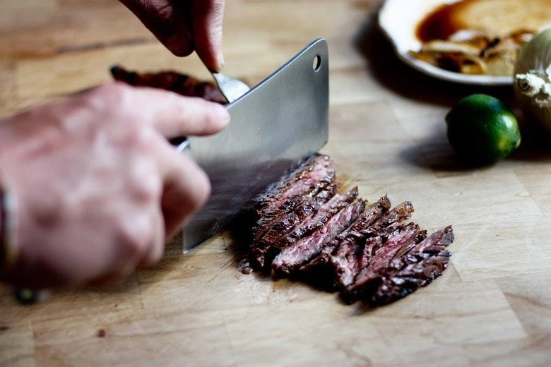Grilled Steak being cut thinly on a cutting board.