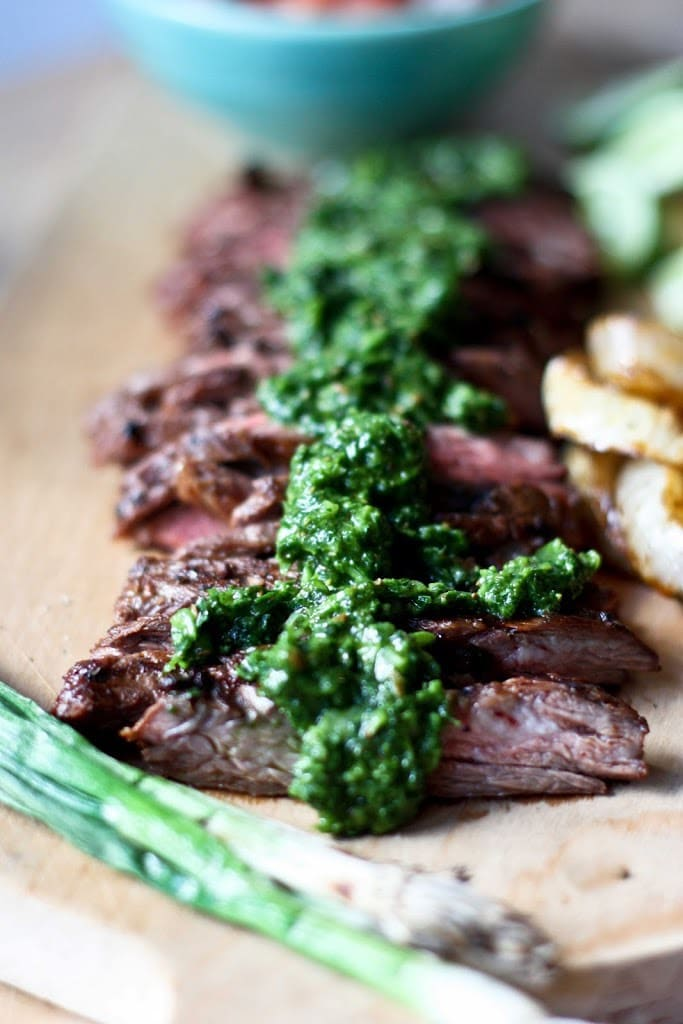 Grilled flank steak on a cutting board, thinly sliced with Chimichurri