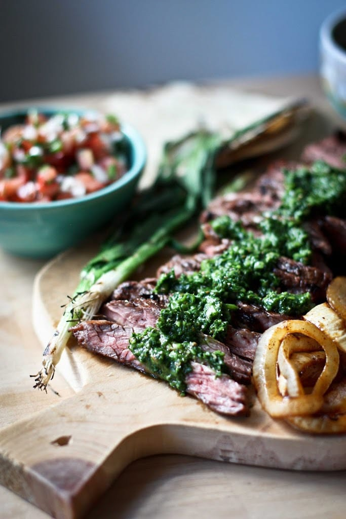Grilled Steak, thinly sliced on a cutting board with Chimichurri sauce