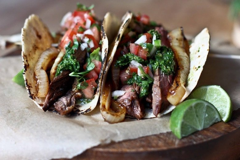Two Steak Tacos with all the toppings on parchment paper