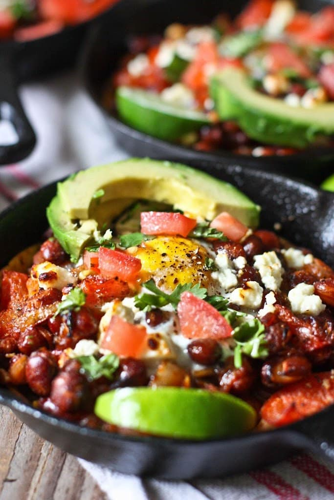 Huevos Rancheros Skillet Eggs- with hearty beans, crispy tortilla, avocado and fresh tomato and cilantro...so simple and tasty! | www.feastingathome.com