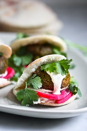 Falafels with Tahini Sauce. This authentic recipe is made with soaked, uncooked chickpeas and hands-down has the BEST texture and flavor! So easy! Bake them or pan-sear them. Great in wraps, bowls, or salads. |  #falafel #falafels #falafelrecipe #falafelsalad, #bowl #veganfalafelrecipe #bakedfalafel #vegan #easyfalafel