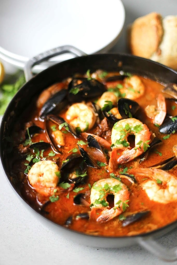 Summer Seafood Stew in a light and flavorful tomato-fennel broth with smoky chorizo. Serve with Crusty Bread to mop up all the flavorful juices! #bouillabaisse #fishstew #seafoodstew #stew #cioppino #seafood #fish #fishsoup #seafoodsoup