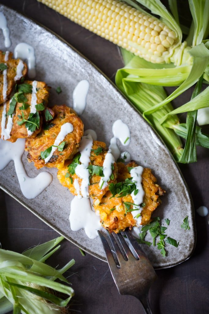 Spicy Corn Fritters with Cilantro Cream - an easy delicious recipe that works as an appetizer or vegetarian main! www.feastingathome.com #cornfritters #corncakes
