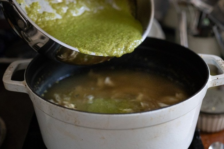 pouring the green sauce into the broth with the chicken