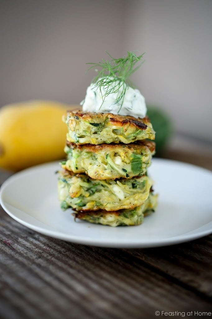 Zucchini Fritters with dill, feta and Tzatziki Sauce, a simple easy way to use up summer squash and zucchini! Healthy and light! #zucchinifritters #zucchinicakes #zucchinirecipes