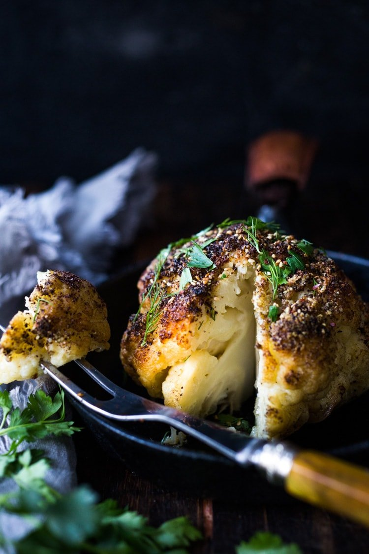 Whole Roasted Cauliflower with Zaatar Spice and Tahini Sauce- a healthy vegan side dish bursting with Middle Eastern flavor. Easy and delicious! #roastedcauliflower #cauliflower #veganside #tahinisauce #zaatar #tahinicauliflower