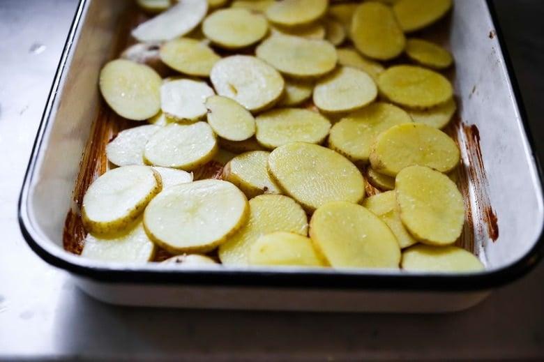 potatoes layered over the marinade
