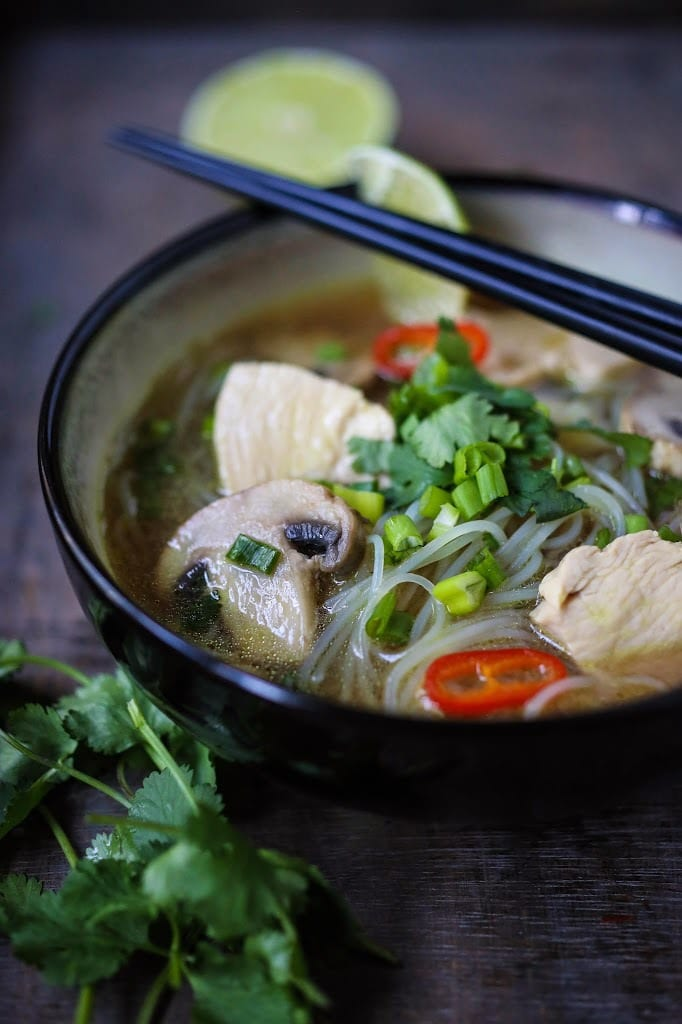 A steaming bowl of Thai Chicken Noodle Soup infused with lemongrass and ginger.  A healthy, low fat, gluten-free meal, full of amazing Thai flavors!
