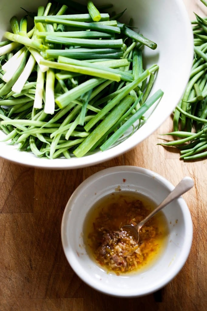 Bagna Cauda Recipe....Charred Green Beans with Bagna Cauda- an Itailian Marinade with olive oil, anchovies, garlic and chili flakes. Roasted in the oven with scallions and lemon zest, these green beans are full of umami flavor. | www.feastingathome.com