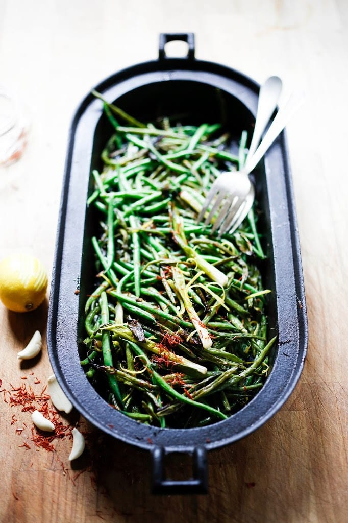 Charred Green Beans with Bagna Cauda- an Itailian Marinade with olive oil, anchovies, garlic and chili flakes. Roasted in the oven with scallions and lemon zest, these green beans are full of umami flavor. | www.feastingathome.com