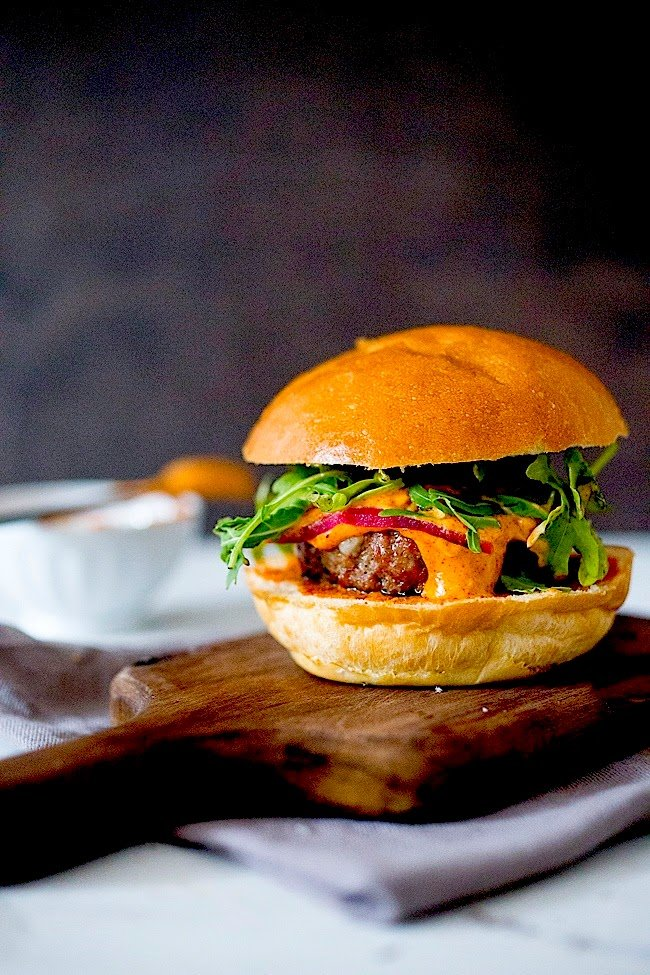 Grilled Lamb Burgers with Harissa Aioli, on a cutting board, completely assembled.