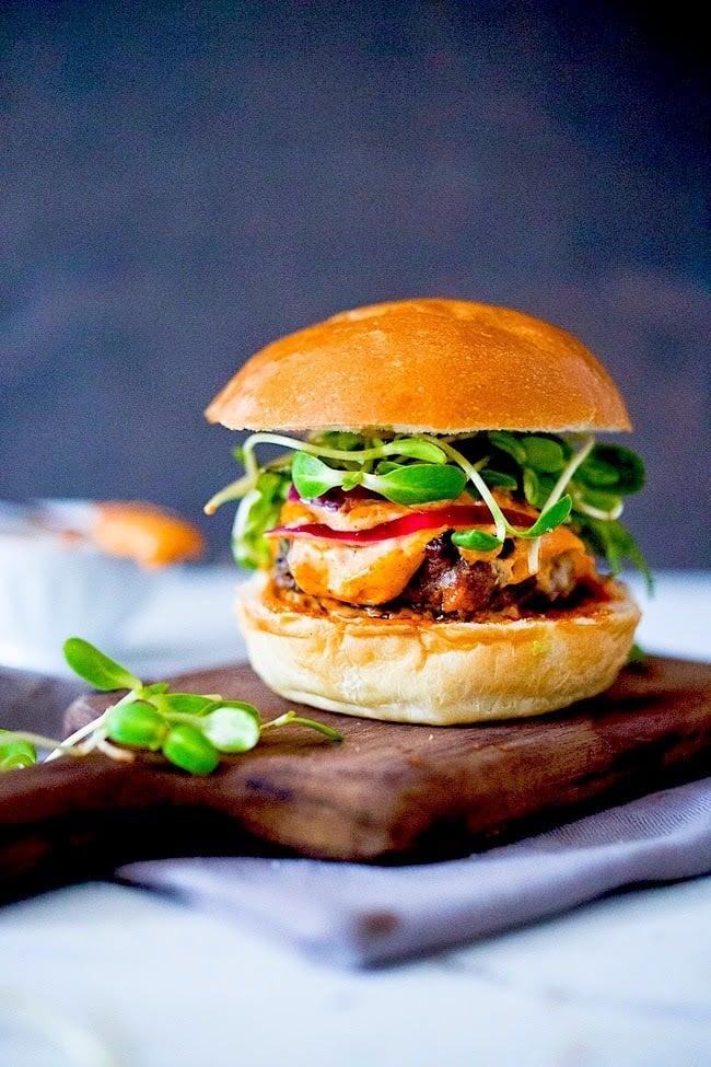 Grilled juicy Harissa Burger with harissa aioli, arugula, pickled onions on Brioche Bun | www.feastingathome.com