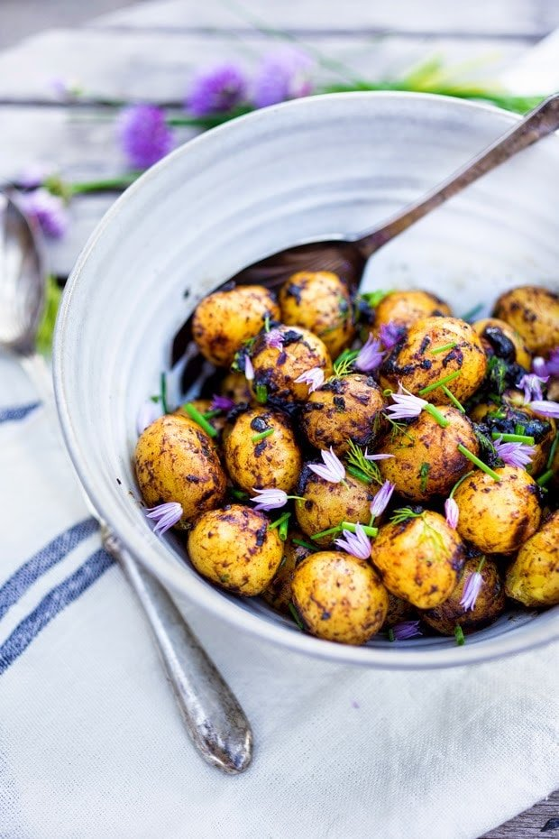 Grilled potato salad with a black garlic vinaigrette...a flavorful, lightened-up potato salad to serve alongside grilled meat or fish! Serve this warm or chilled.  #grilled #potatosalad #blackgarlic #healthypotatosalad #vegan