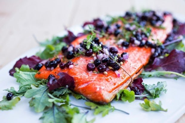 Healthy Grilled Salmon with a fresh Huckleberry shallot relish is the perfect summer meal! Light and delicious and full of flavor, huckleberries are just slightly pickled giving the salmon a wonderful brightness. #grilledsalmon #grilled #huckleberries #huckleberry #salmon #glutenfree