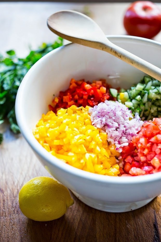 A simple & delicious recipe for Israeli Salad, made with finely chopped vegetables, fresh herbs, lemon and olive oil. Vegan and Gluten Free!   www.feastingathome.com