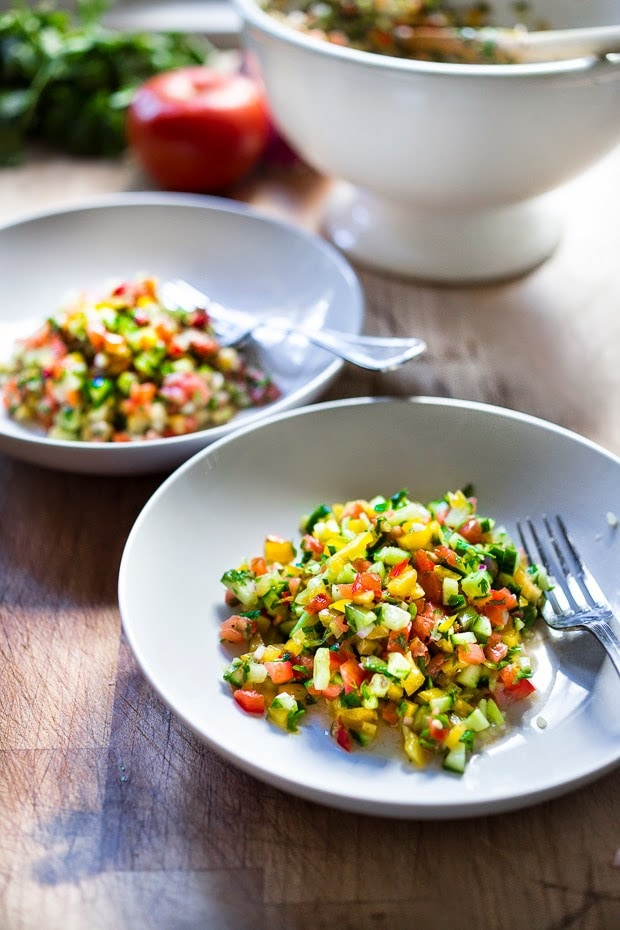 A simple & delicious recipe for Israeli Salad, made with finely chopped vegetables, fresh herbs, lemon and olive oil. Vegan and Gluten Free! | www.feastingathome.com
