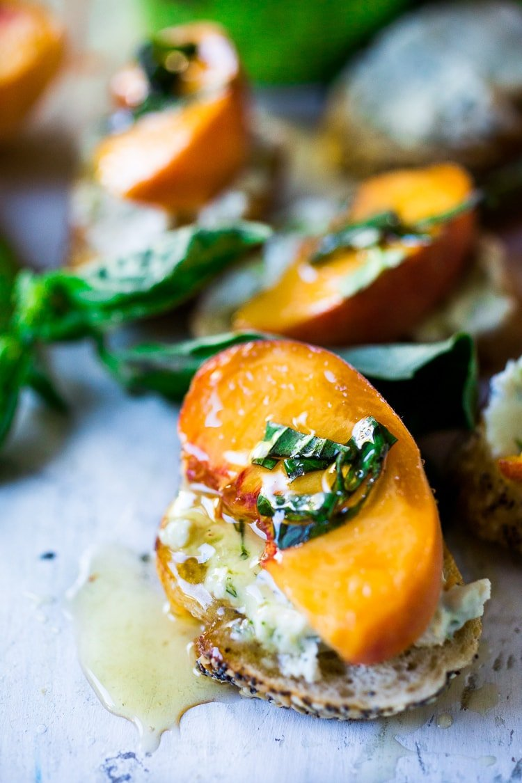 Peach Brushetta with goat cheese, basil and infused honey...a simple delicious appetizer you can make in minutes!| #peach #peachrecipes #bruschetta #peachbruschetta www.feastingathome.com
