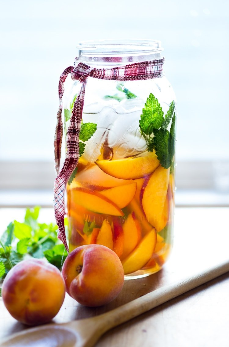 Simple Refreshing Peach Sangria ...a delicious summer cocktail made with white wine and Elder flower liquor (or syrup) that can be made ahead. Perfect for a crowd!  #peachsangria #peach #sangria | www.feastingathome.com