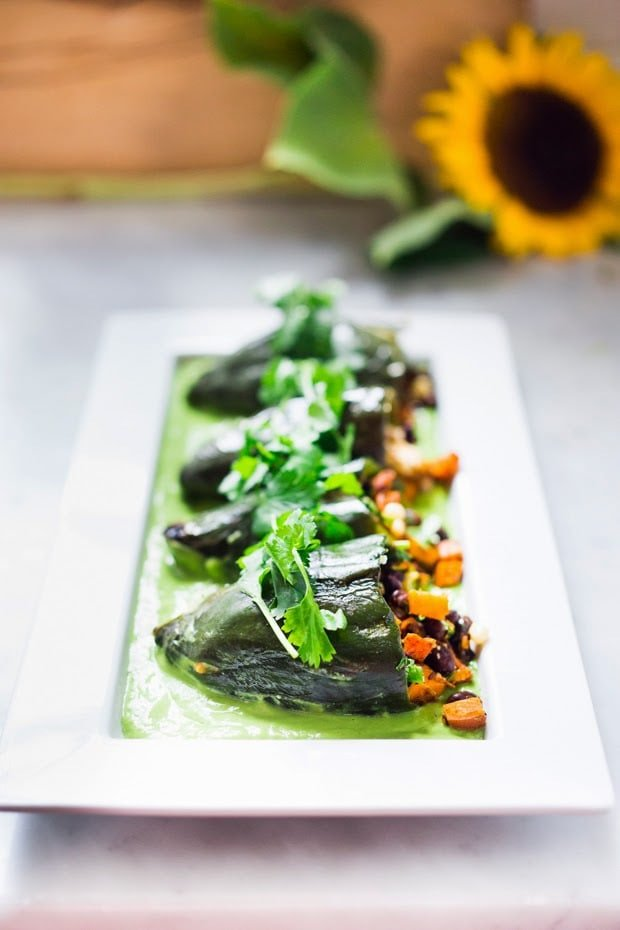 Vegan stuffed poblano peppers filled with sweet potatoes, black beans, corn and cilantro - served over the best thing ever - a flavorful Avocado-Cilantro Sauce which is vegan and has no other added oils or fat.