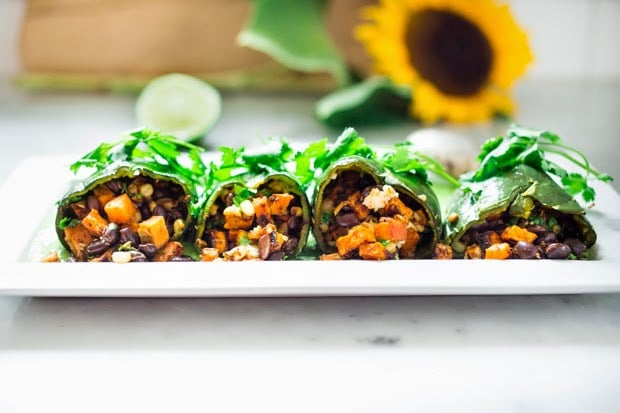 Vegan stuffed poblano peppers filled with sweet potatoes, black beans, corn and cilantro - served over the best thing ever - a flavorful Avocado-Cilantro Sauce which is vegan and has no other added oils or fat. | www.feastingathome.com