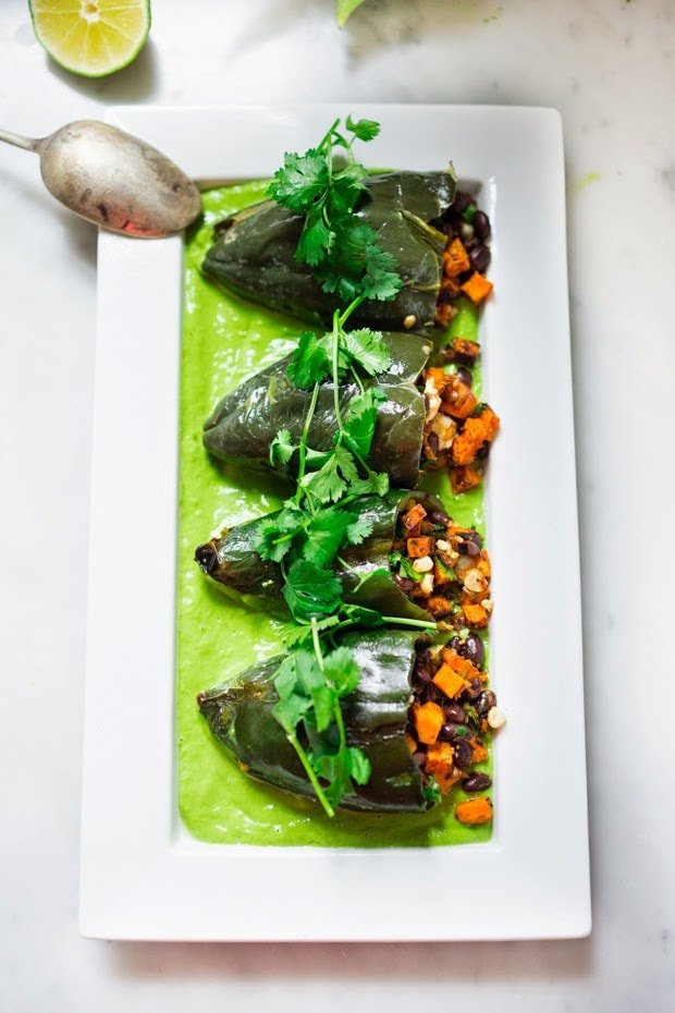 Vegan stuffed poblano peppers filled with sweet potatoes, black beans, corn and cilantro - served over the best thing ever - a flavorful Avocado-Cilantro Sauce which is vegan and oil-free.