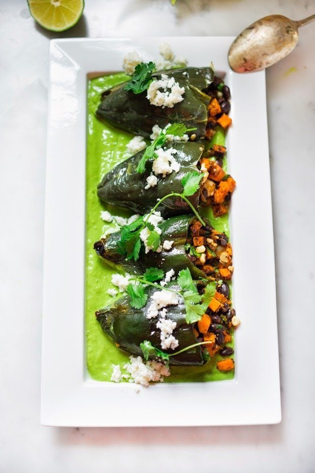 Vegan stuffed poblano peppers filled with sweet potatoes, black beans, corn and cilantro - served over the best thing ever - a flavorful Avocado-Cilantro Sauce which is vegan and has oil-free. | www.feastingathome.com