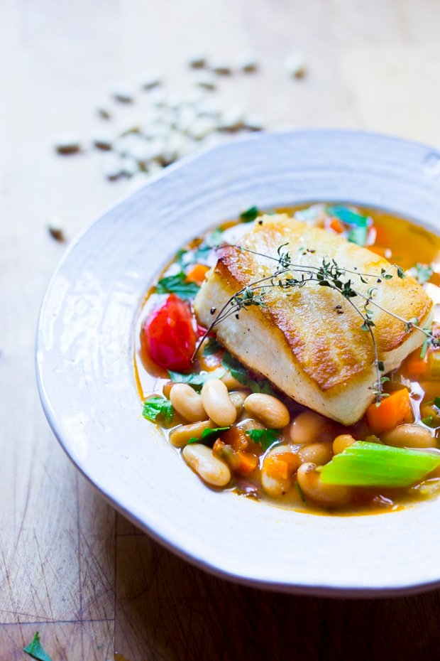 A simple healthy Mediterranean recipe for Sea Bass served over a fragrant Cannellini Bean Stew. Can be made in 30 minutes! | www.feastingathome.com #seabass #cannellinibeans