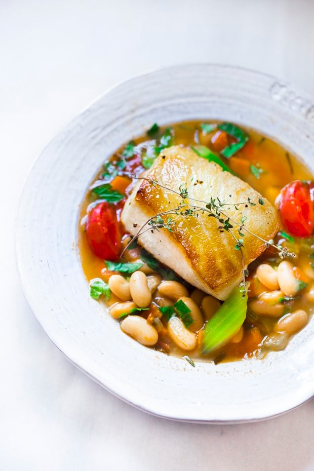 A simple healthy Mediterranean recipe for Sea Bass served over a fragrant Cannellini Bean Stew. Hearty and flavorful this easy dinner can be made in 30 minutes!  #seabass #cannellinibeans
