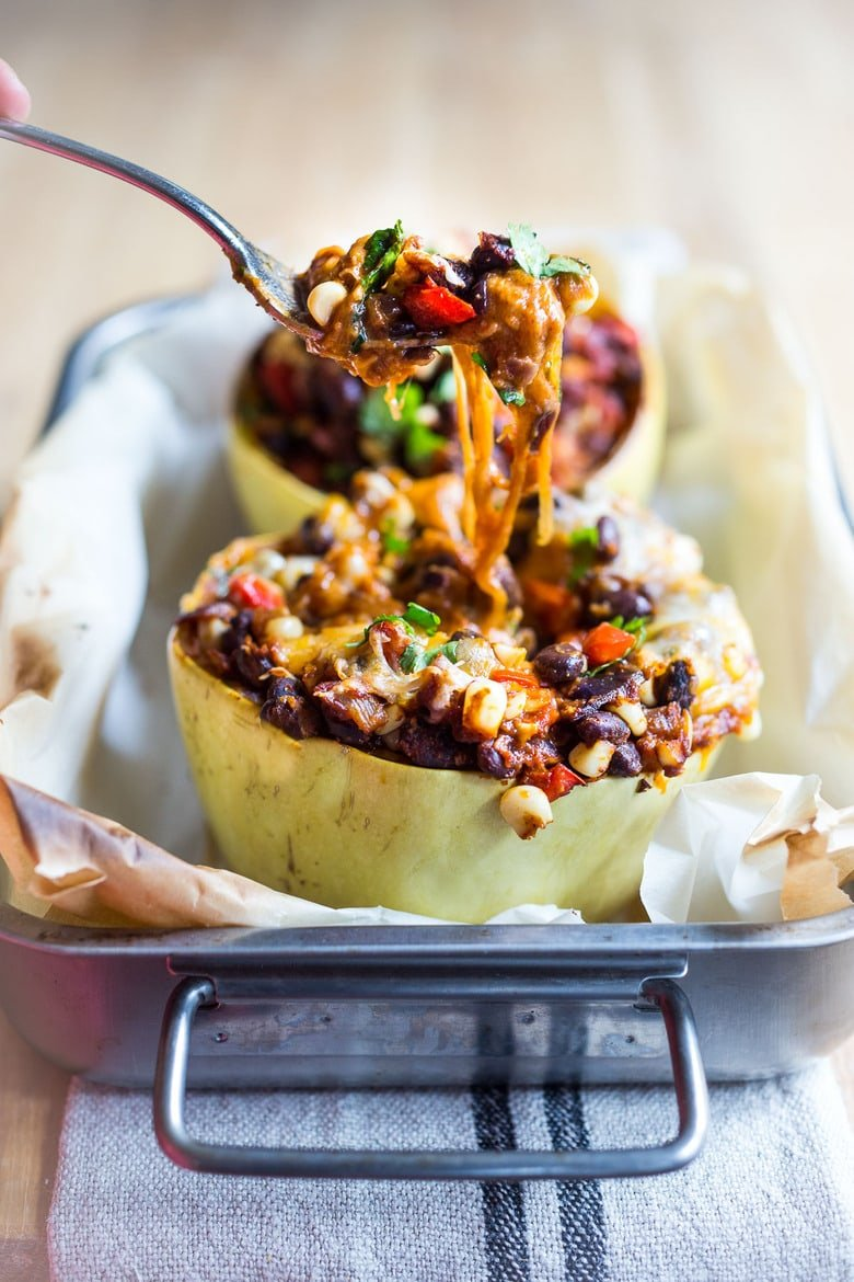 Enchilada Stuffed Spaghetti Squash! Roasted spaghetti squash stuffed with peppers, corn, black beans, cheese, enchilada sauce and Mexican seasonings. #enchiladas #spaghettisquash #stuffedspaghettisquash