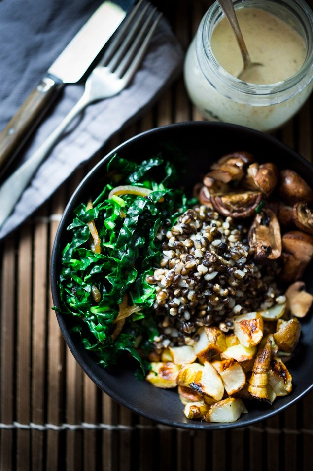 This Roasted Sunchoke and Black Nile Barley Bowl, with kale, mushrooms and parsnips & a Zaatar spiced Tahini Sauce is perfect for fall! Vegan and Nutritious! | www.feastingathome.com