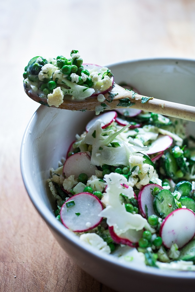 Shaved Cauliflower Salad with spring peas, radishes, cucumber, mint and a delicious Yogurt Dressing. The thinly sliced cauliflower is raw and marinates in the flavorful dressing. #cauliflowersalad #springsalad #yogurtdressing #raw #rawsalad