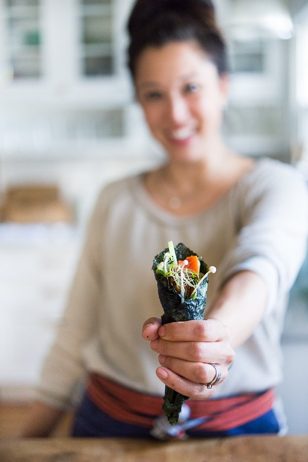 Nami Meier and her Healthy Smoked Salmon Hand rolls filled with avocado, cucumber and smoked salmon...an affordable fun way to feed a large gathering! | www.feastingathome.com