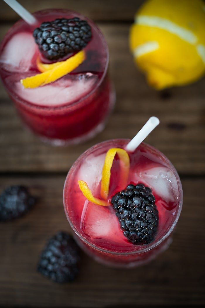 A refreshing summer cocktail called the Blackberry Bramble with muddled fresh blackberries, gin, lemon juice and soda or ginger brew! | www.feastingathome.com