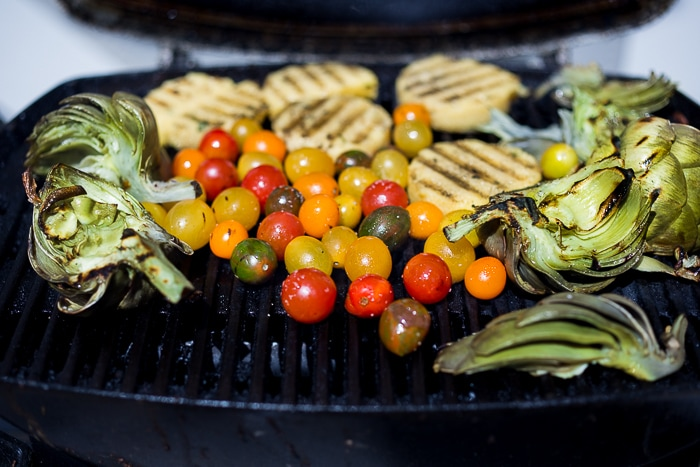 Grilled Artichoke and Polenta with blistered tomatoes, pesto, capers and fresh basil -served family style! An easy healthy rustic meal, perfect for summer nights on the patio! Vegan and GF   www.feastingathome.com  #grilledartichokes #artichokes #grilled #easy #vegan